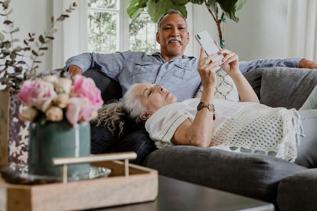 Пожилая пара с помощью телефона на диване