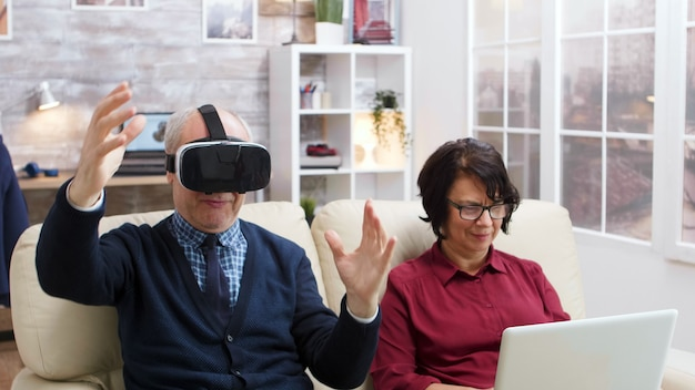Elderly couple using modern technology to watch movies. senior with virtual reality goggles. old lady with laptop.