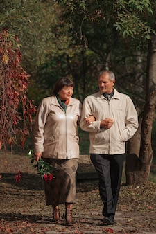 An elderly couple walks in an autumn park holding hands, holding a bouquet of red roses.