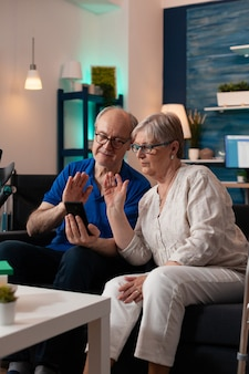 スマートフォンを使用してビデオ通話のウェブカメラで手を振っている老夫婦