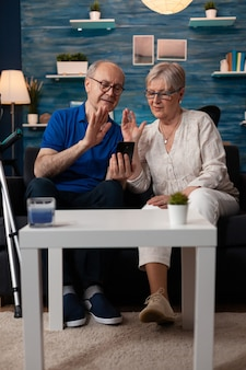 Elderly couple waving at video call webcam using smartphone