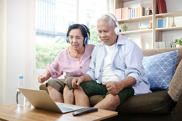 An elderly couple wearing headphones