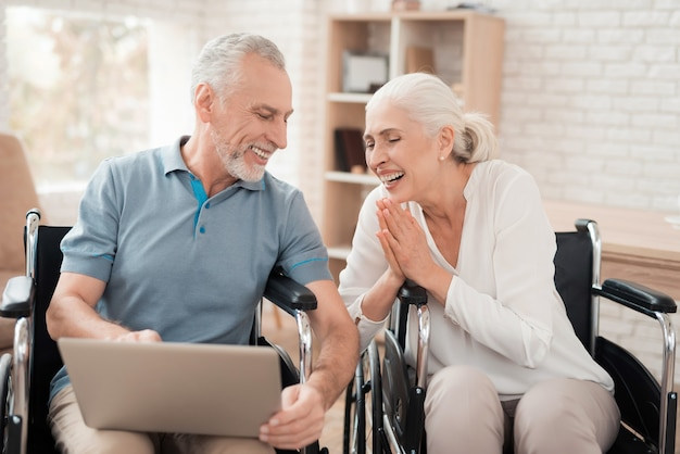 Elderly couple in wheelchairs looks at laptop screen.