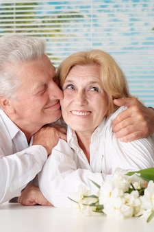 Пожилая пара с цветами, отдыхая дома