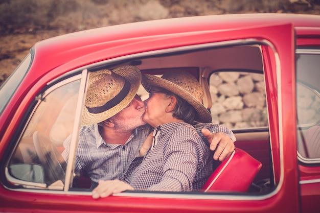 帽子、眼鏡、灰色と白の髪、カジュアルなシャツ、休暇中のヴィンテージの赤い車で時間と人生を楽しんでいる高齢者のカップル。風の強いspに浸って笑っている陽気な携帯電話で