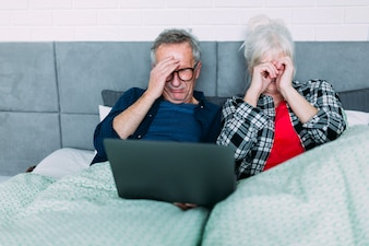 Elderly couple with headache in bed with laptop