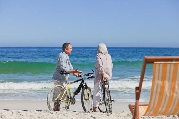 ビーチで自転車に乗っている高齢者のカップル