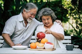 年配のカップルが遊ぶことおよびフルーツを食べる