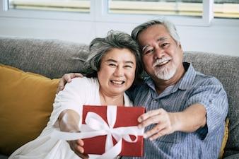 年配のカップルリビングルームでのサプライズとギフトボックス