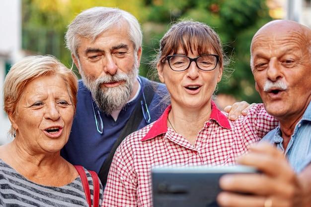 スマートフォンでselfieを取る高齢者のカップル