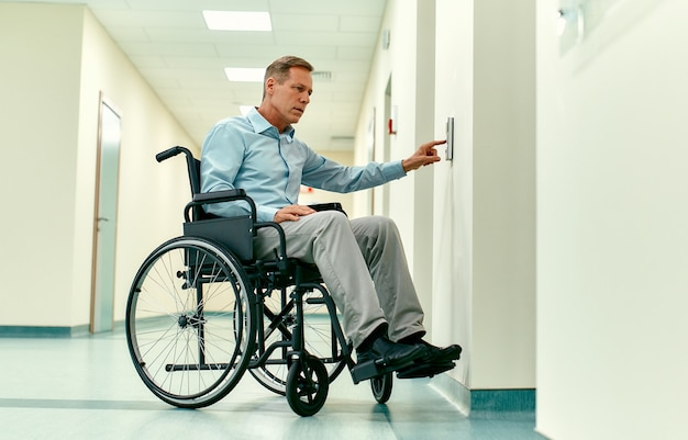 An elderly disabled man in a wheelchair presses the call button for the elevator in a modern clinic.