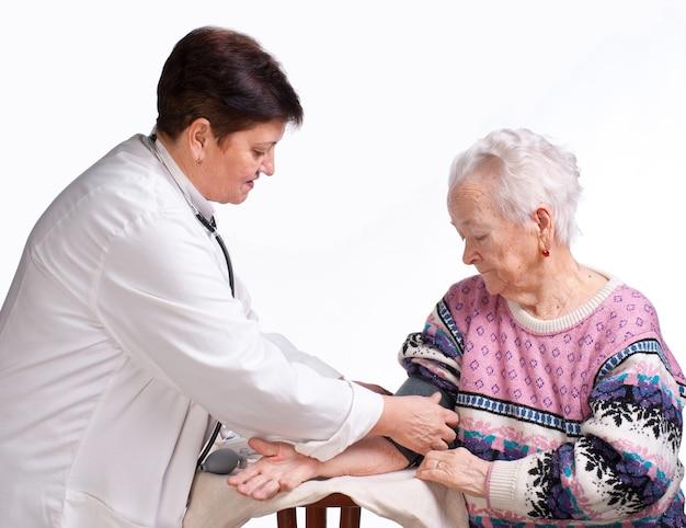 노인 의사와 환자는 흰색 바탕에. 압력 측정.