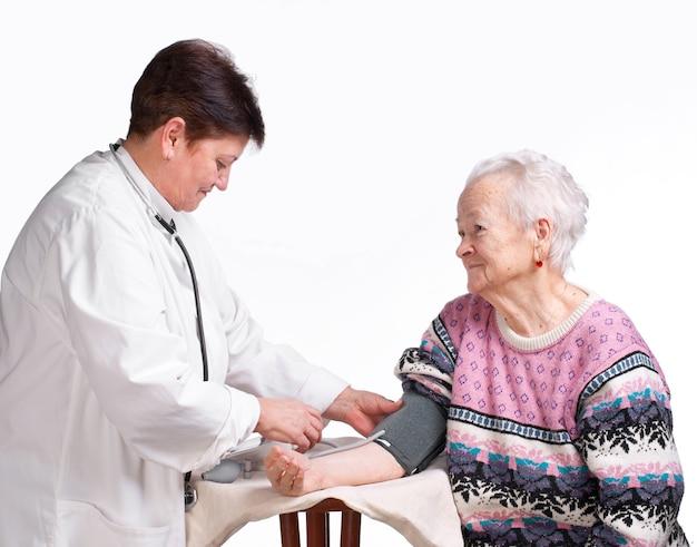 白い背景の上の高齢の医師と患者。圧力の測定。
