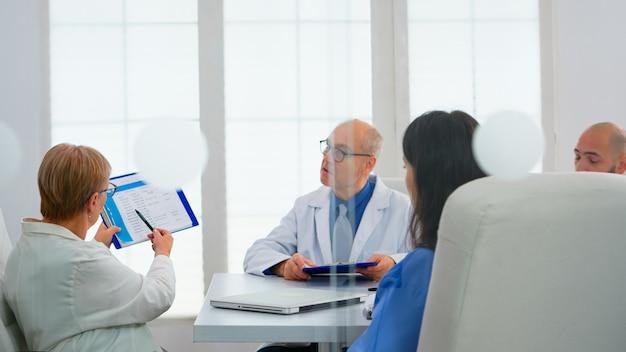 病院の会議室で、病気の患者のリストを提示するクリップボードを指して医学的問題について話し合う高齢の医師。病気の症状を示す医師のチーム