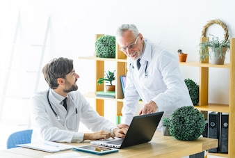 Elderly doctor helping young colleague with work