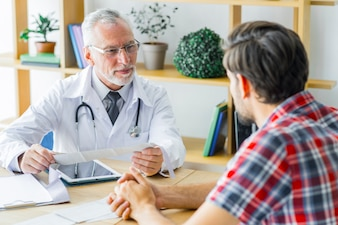 Elderly doctor listening to young patient