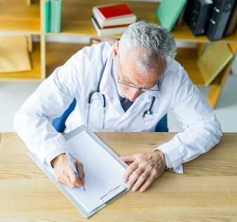Elderly doctor making notes on clipboard