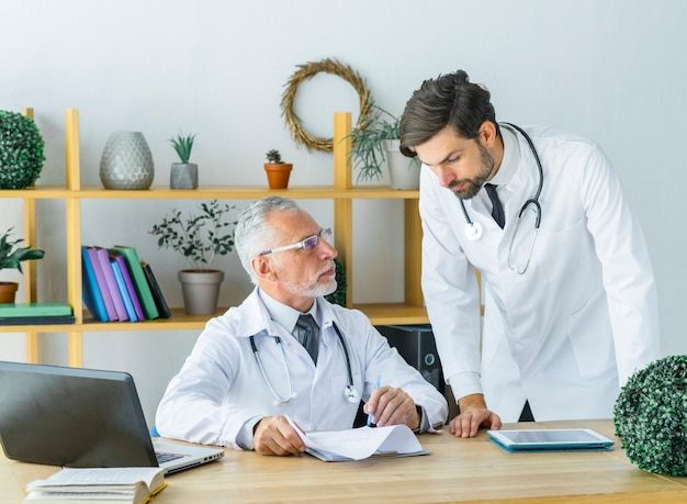 Elderly doctor showing notes to young colleague