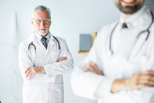 Elderly doctor standing behind anonymous colleague