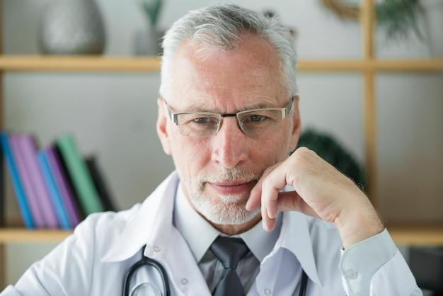 Пожилой врач, думающий в офисе
