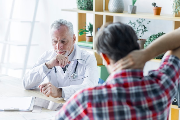 Elderly doctor thinking while talking with patient