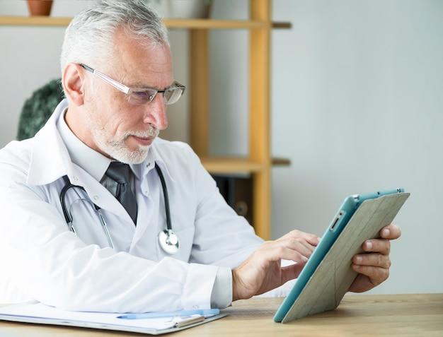 Пожилой врач, используя планшет в офисе