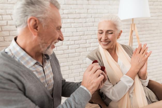 Elderly elegant man offers one's hand to mature pretty woman