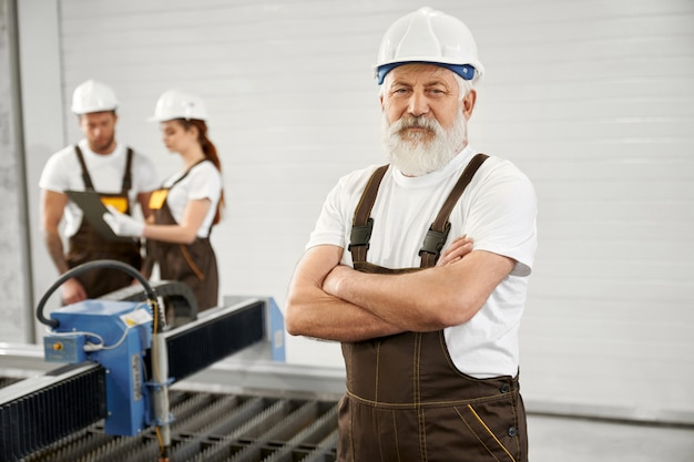 Elderly engineer posing on metalworking factory.