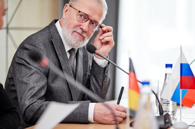 소송에서 노인 임원 정치인 남자는 회의에 앉아 사람들의 의견을 듣고 사무실에서 마이크를 사용하여 아이디어를 공유합니다. 국제 회의, 정상 회담