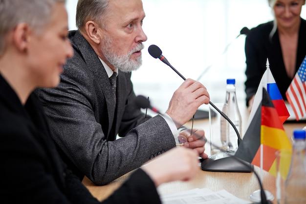 スーツを着た年配の政治家の男性が会議に座って、オフィスのマイクを使って人々の意見を聞いたり、アイデアを共有したりしています。国際会議、首脳会談
