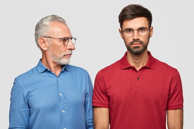 Un anziano maschio esperto guarda attentamente suo figlio adulto, dà consigli, indossa occhiali e camicia blu formale, ha buoni rapporti