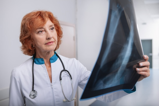高齢者の女性医師が患者の肺のx線スキャンを調べる