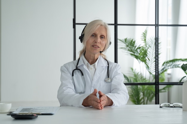 Elderly female doctor in a white medical coat looking at the camera and talking with headphones sitting in a hospital office
