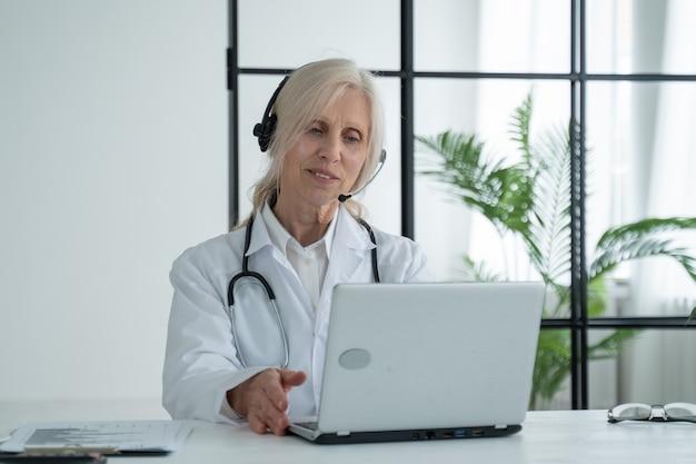 Пожилая женщина-врач со стетоскопом в лабораторном халате и гарнитуре общается по видеосвязи с пациентом через ноутбук