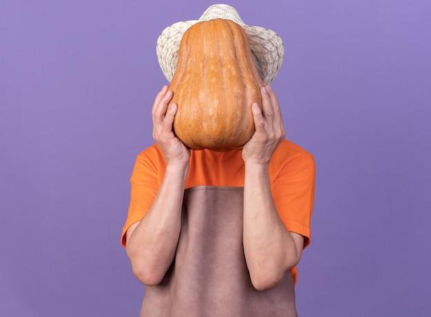 Donna anziana giardiniere che indossa cappello da giardinaggio tenendo la zucca davanti al viso