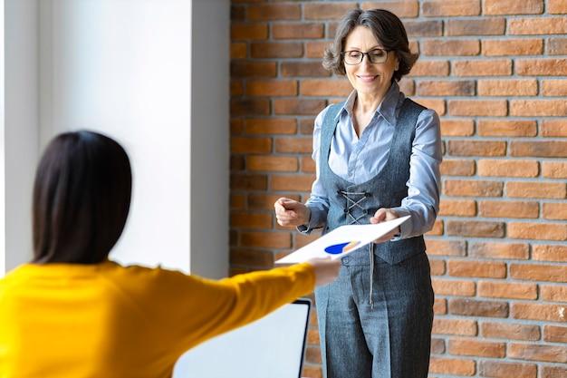 Пожилая женщина-наставник-лидер обучает сотрудника анализу продаж или объясняет новую бизнес-стратегию на встрече в офисе