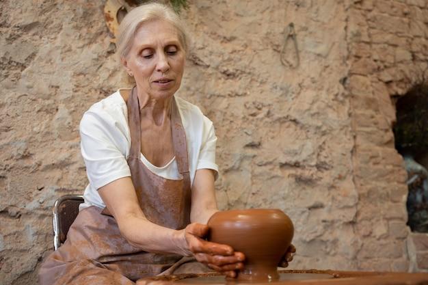 Пожилая женщина-гончар в фартуке делает горшок в гончарной мастерской