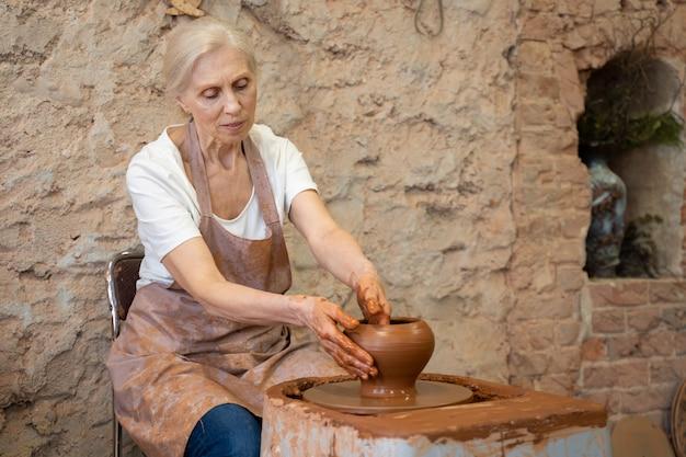 Пожилая женщина-гончар работает на гончарном круге, сидя в своей мастерской