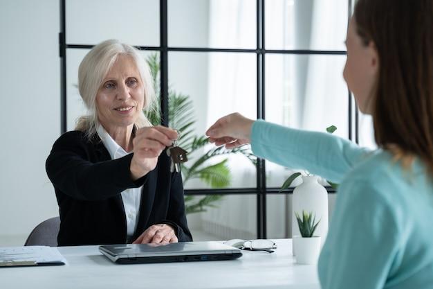 Пожилая женщина-агент по недвижимости передает ключи от квартиры клиентке