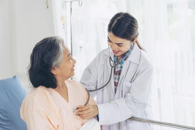 Пожилая женщина улыбается с врачом и посещение старшей пациентки в больничной палате