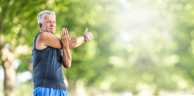 Elderly fit man stretches his arm on a summer day outdoors, wearing watches and earphones.