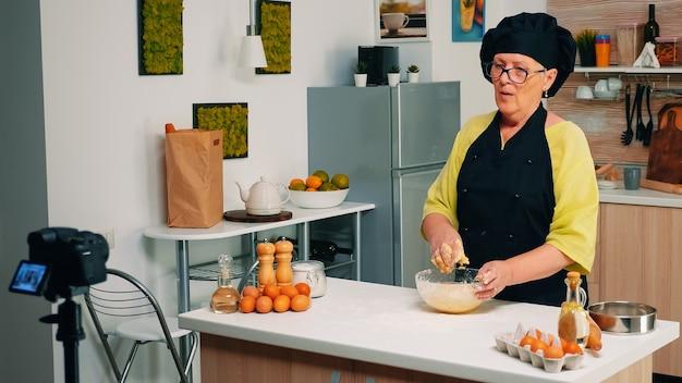 Пожилой кулинарный блогер в прямом эфире из домашней кухни готовит тесто для хлеба. блогер на пенсии, повар, влиятельный человек, использующий интернет-технологии, снимает блог в социальных сетях с помощью цифрового оборудования