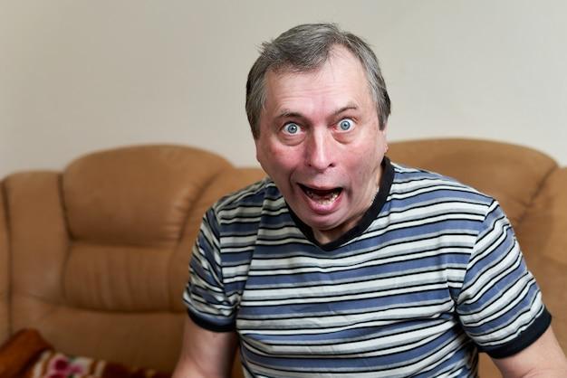 카메라를 찾고 소파에 앉아있는 동안 노인 괴물 얼굴 만들기. 감정 표현하기