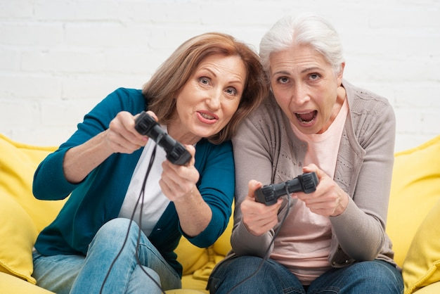Elderly friends playing with controllers
