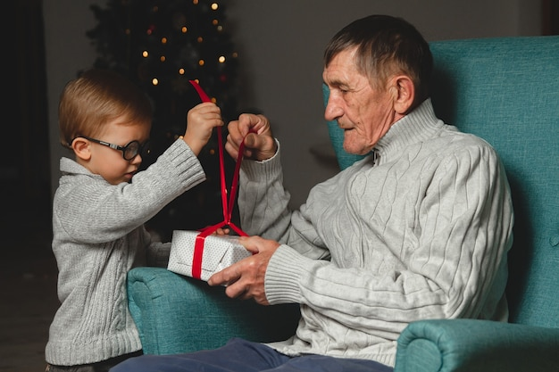 Пожилой дедушка и его маленький внук дарят