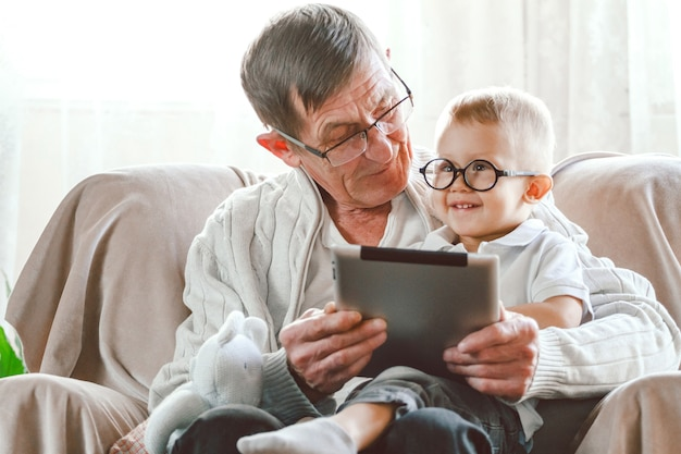 Elderly grandfather and his little grandson use a tablet device