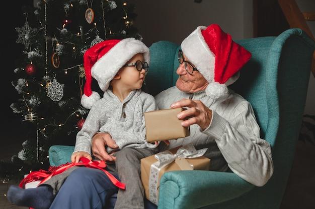 Пожилой дедушка с внуком в шляпах санты дарят и открывают рождественские подарки