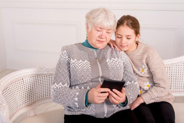 Elderly grandma reading with her granddaughter