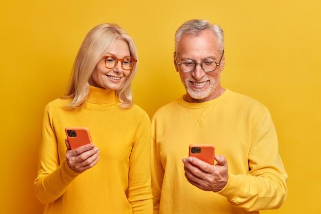 노인 할머니와 할아버지는 스마트 폰 장치에서 함께 사진을 봅니다. 캐주얼 한 노란색 터틀넥을 입고 실내에서 포즈를 취하는 재미있는 재미있는 비디오를 온라인으로 시청하십시오.