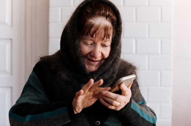 An elderly grandmother holds a mobile phone for the first time